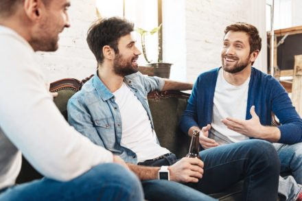 Communication with friends. Nice joyful positive man laughing and chatting with each other while having a great time together
